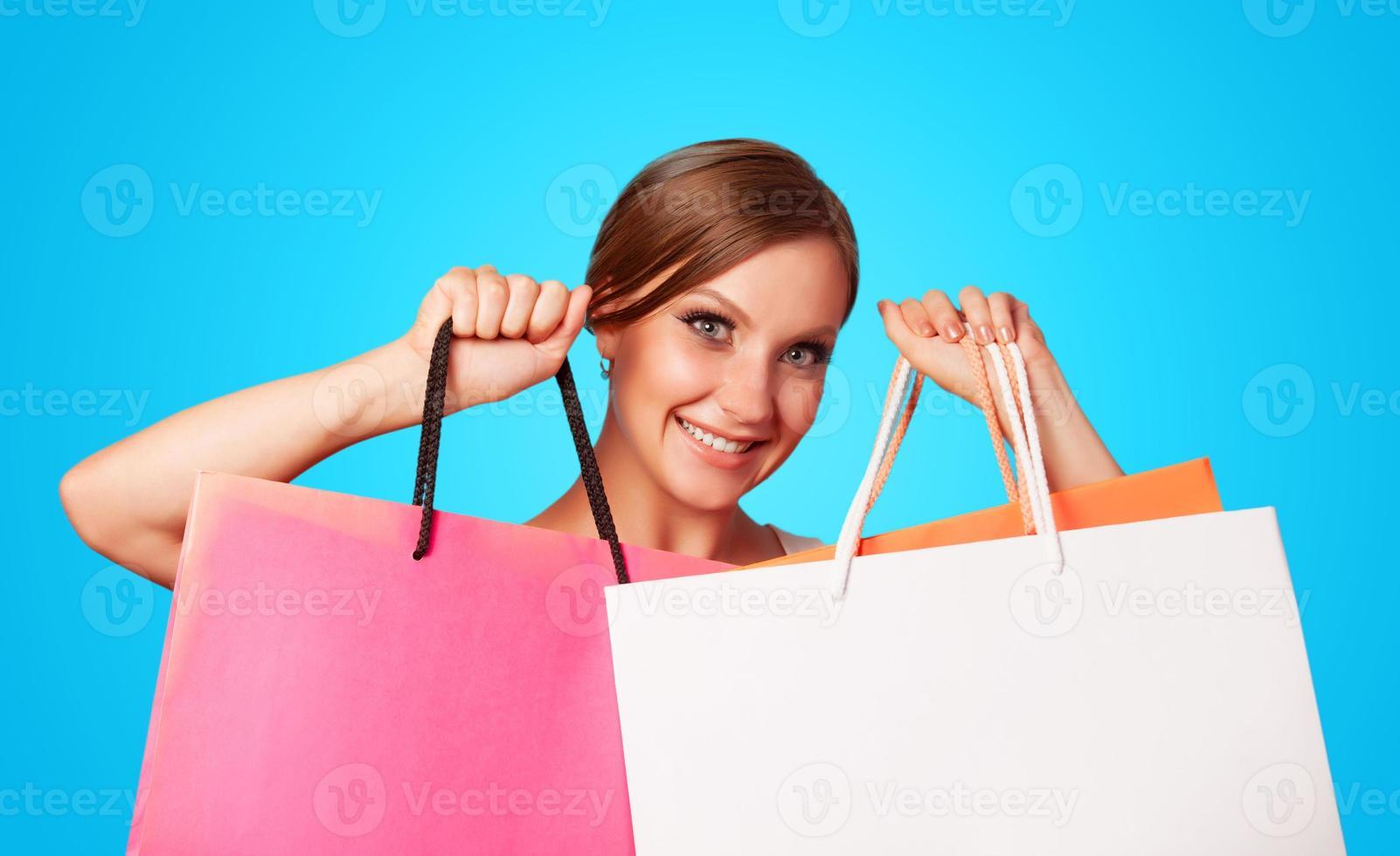 brunette meisje met boodschappentassen op blauwe backgorund. foto