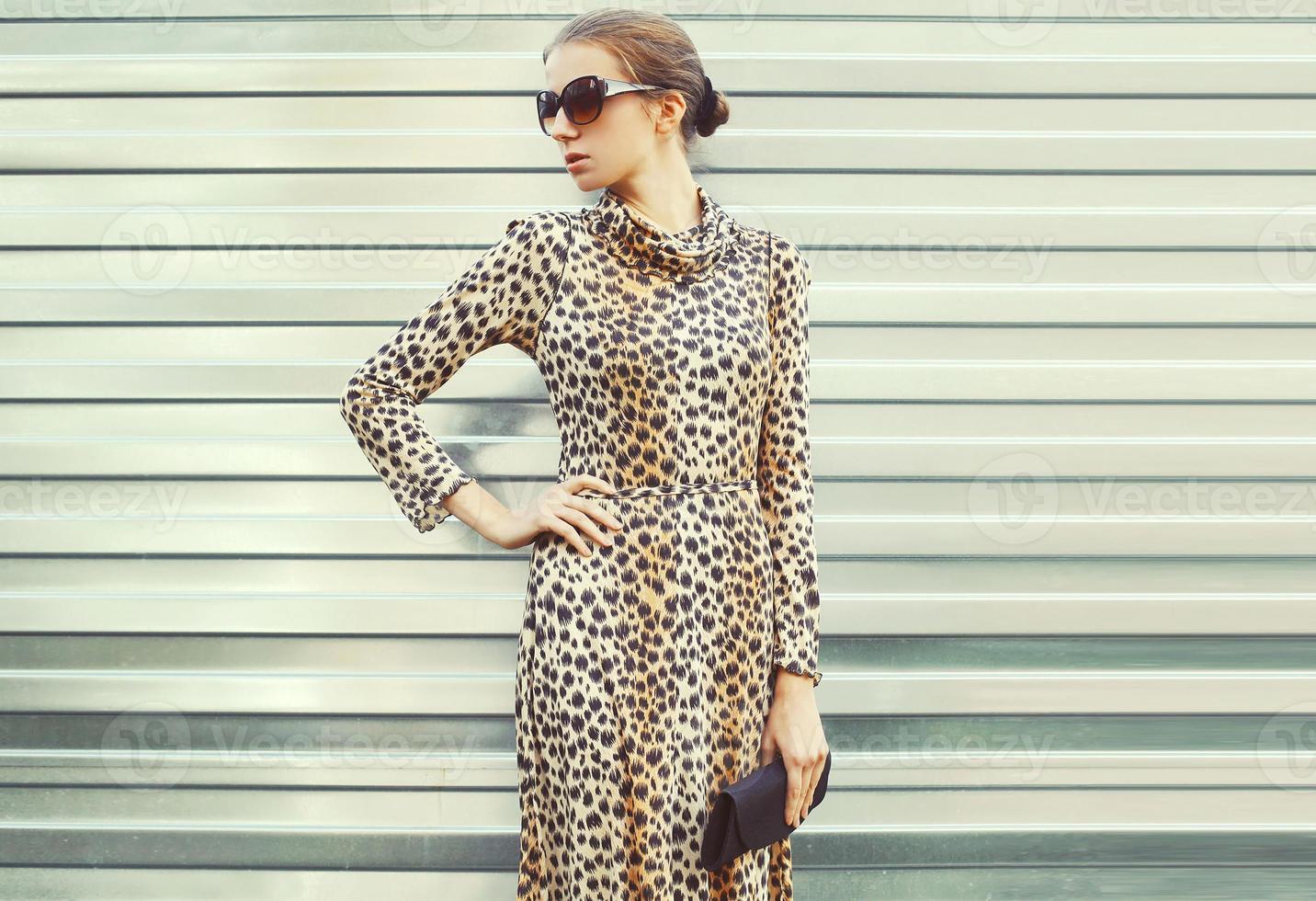 mode mooie vrouw in zonnebril en luipaardjurk met handba foto