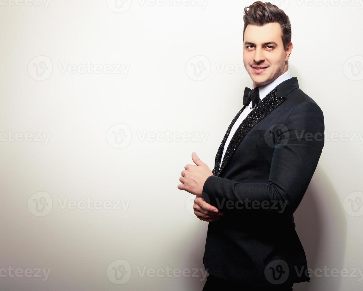 elegante jonge knappe man in zwarte luxe kostuum. foto