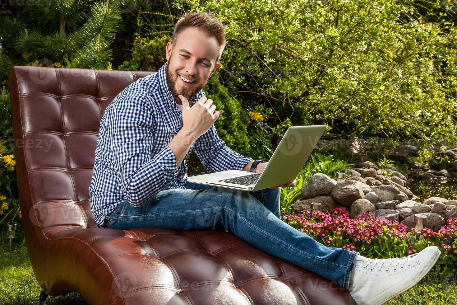 jonge knappe man zitten in luxe sofa met notebook. foto