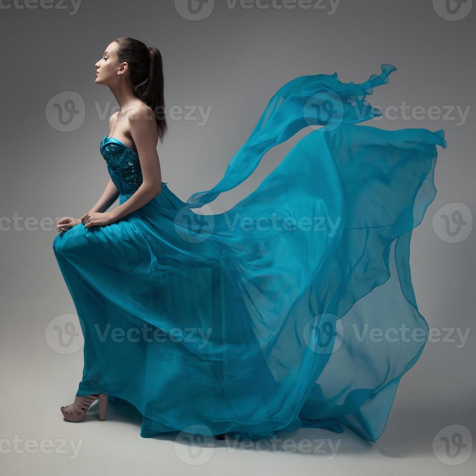 mode vrouw in fladderende blauwe jurk. grijze achtergrond. foto