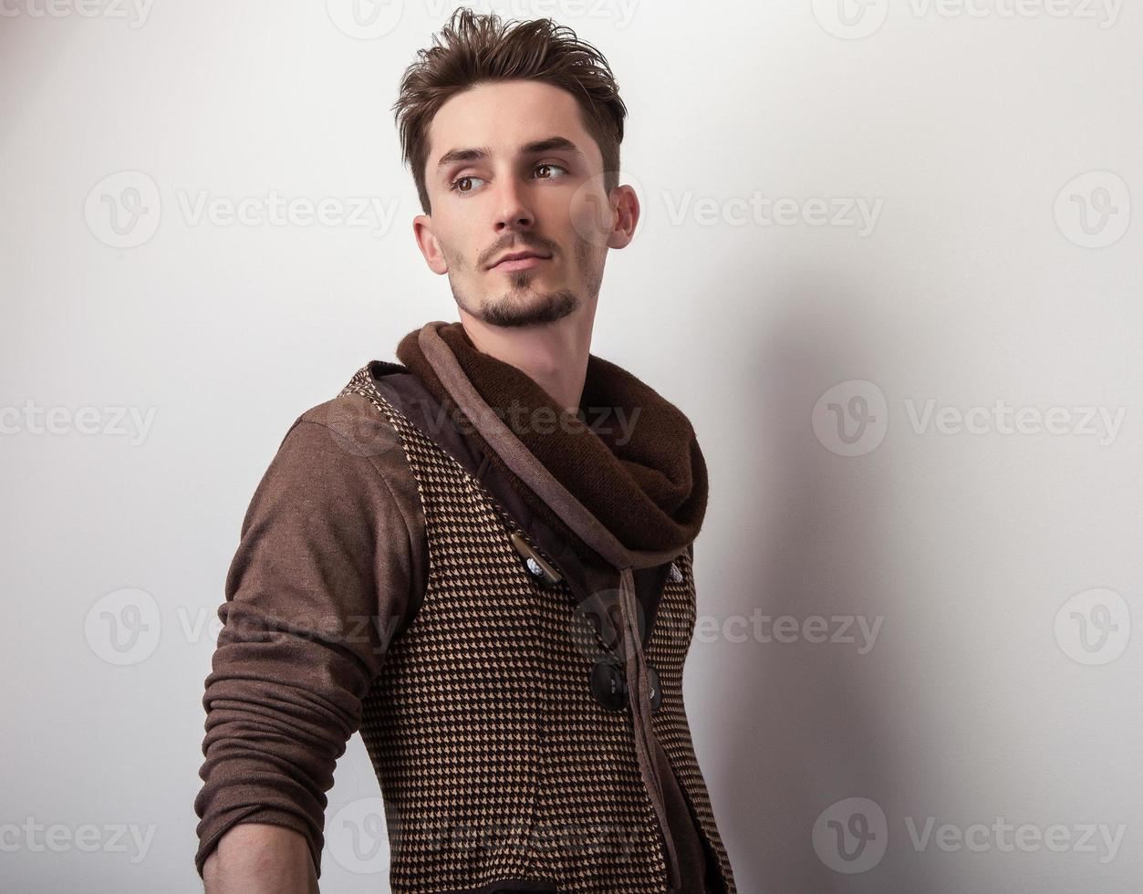 aantrekkelijke jonge man in een bruine trui poseren in studio. foto