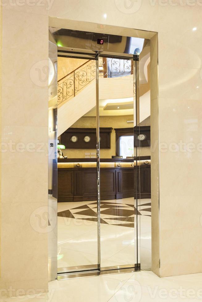 receptie van het hotel weerspiegeld op de liftdeur foto
