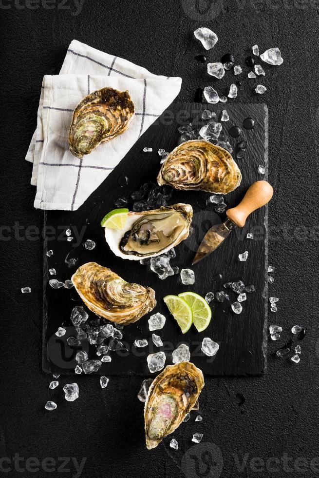 verse oesters op een zwarte stenen plaat bovenaanzicht foto
