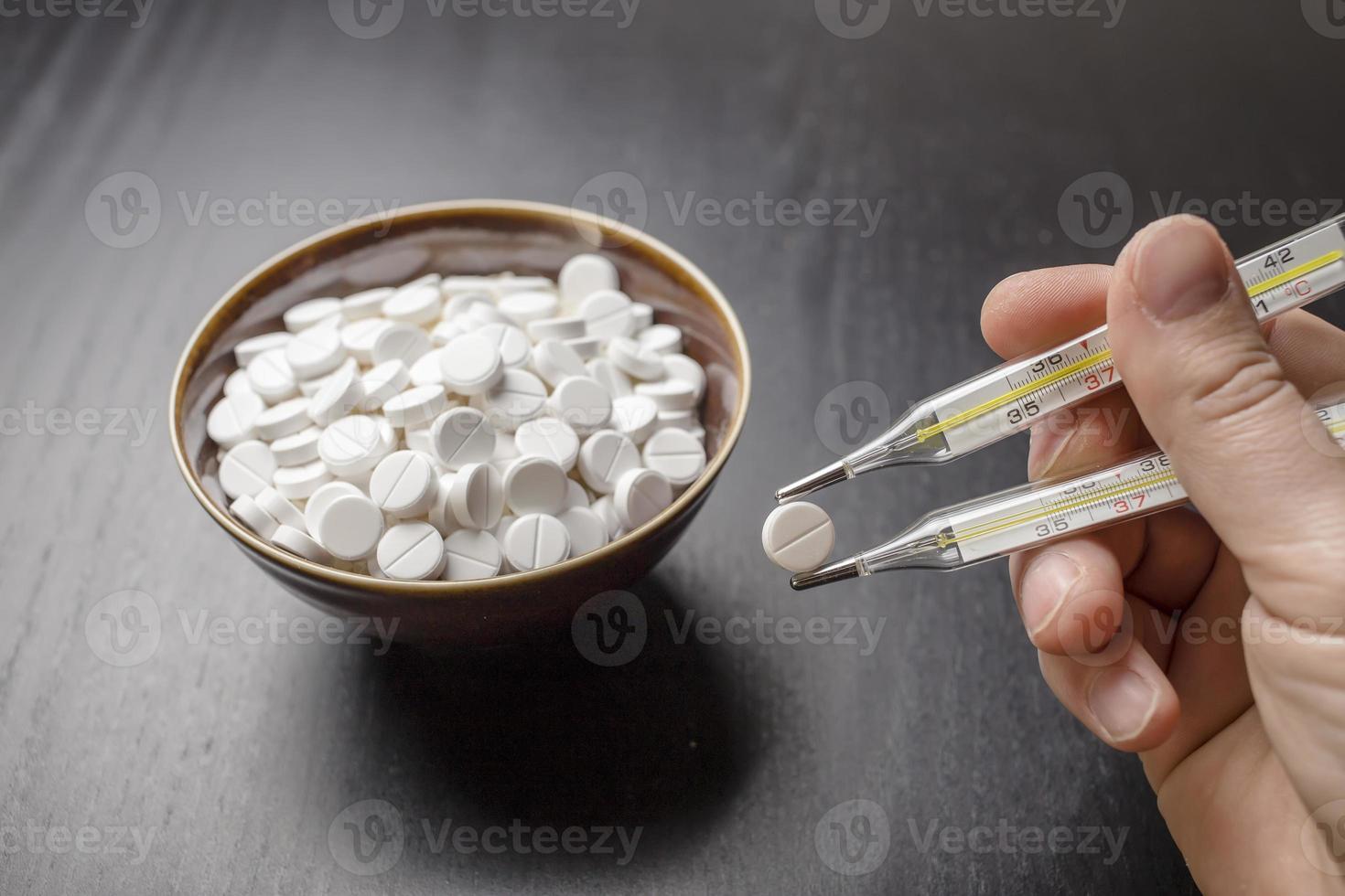 man, drugtabletten, kom en twee medische thermometer zoals chopst foto