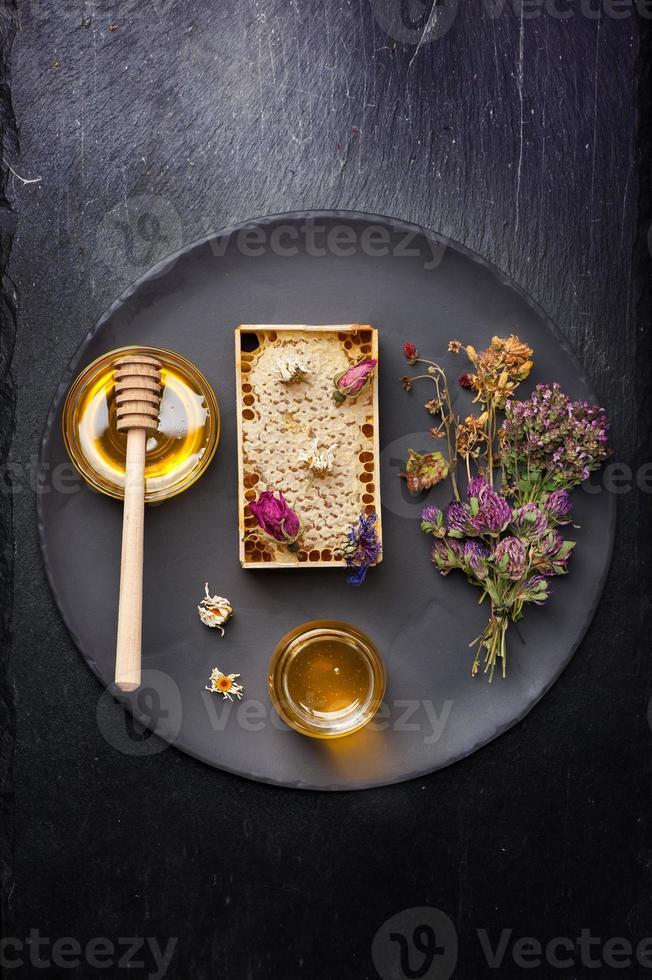 honing en gedroogde kruiden op donkere achtergrond foto
