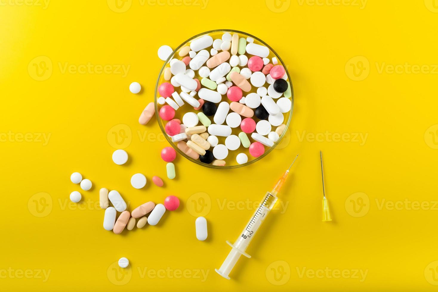 spuit en kleurrijke pil en capsules op achtergrond foto
