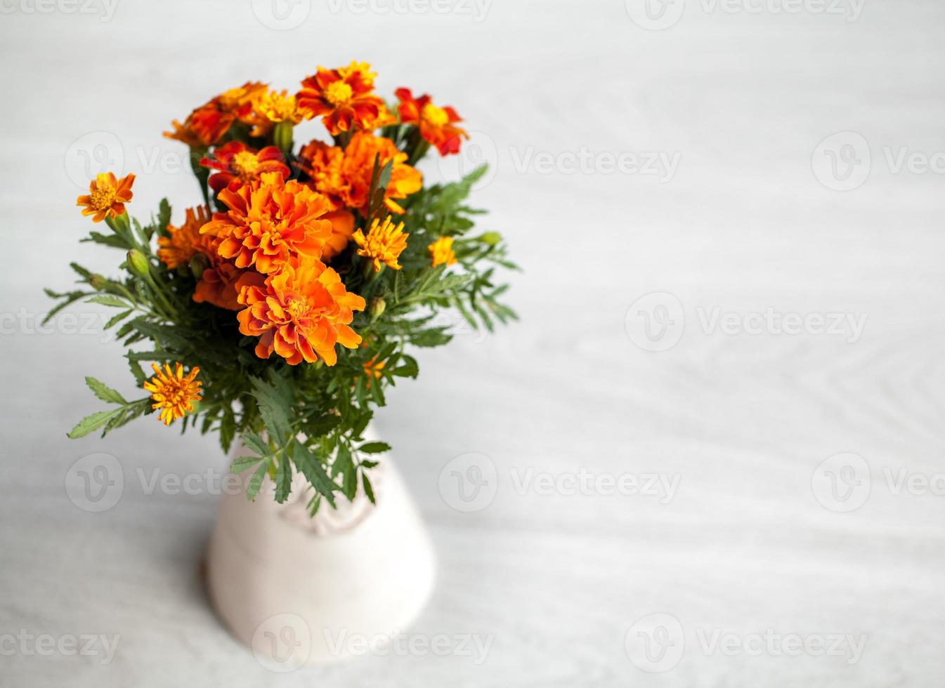 goudsbloemen bloemen in vaas op grijze achtergrond foto