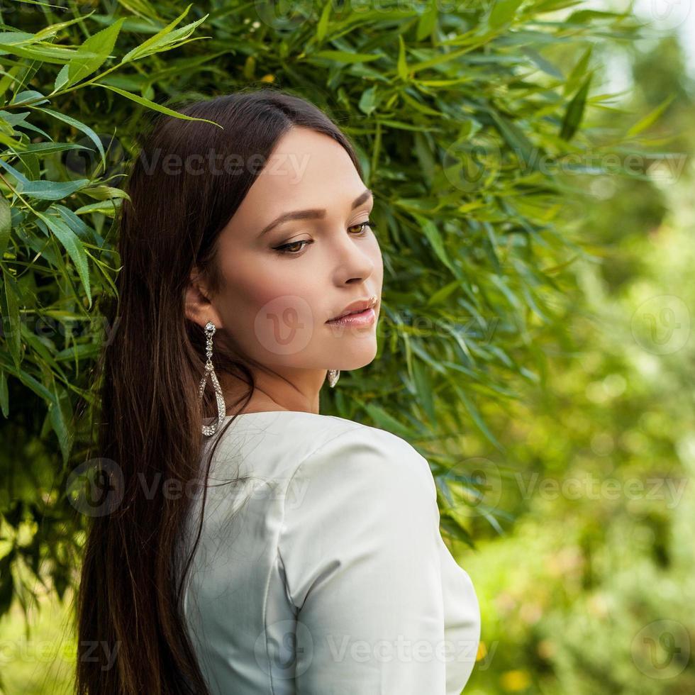 buitenshuis portret van mooi jong meisje in luxe witte jurk. foto