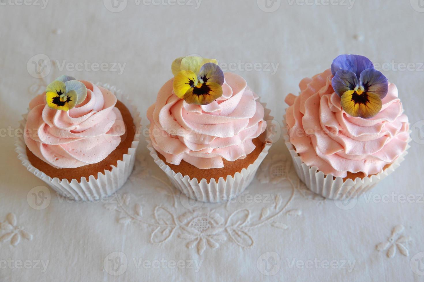 zelfgemaakte roze frosting vanille cupcakes met eetbare bloemen foto