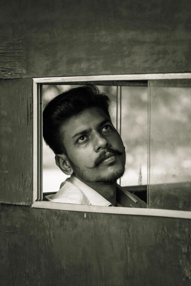 jonge man kijkt door raam foto