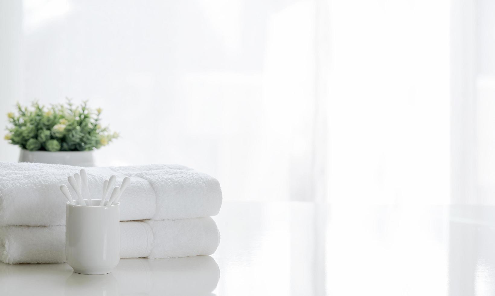 witte handdoeken op een tafel met een plant foto