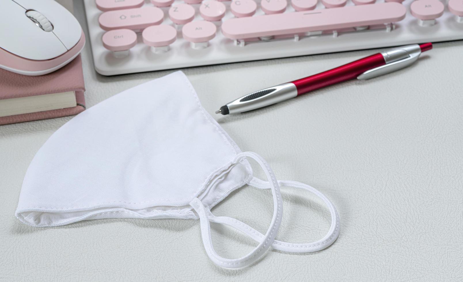 gezichtsmasker op een bureau met een toetsenbord en een pen foto