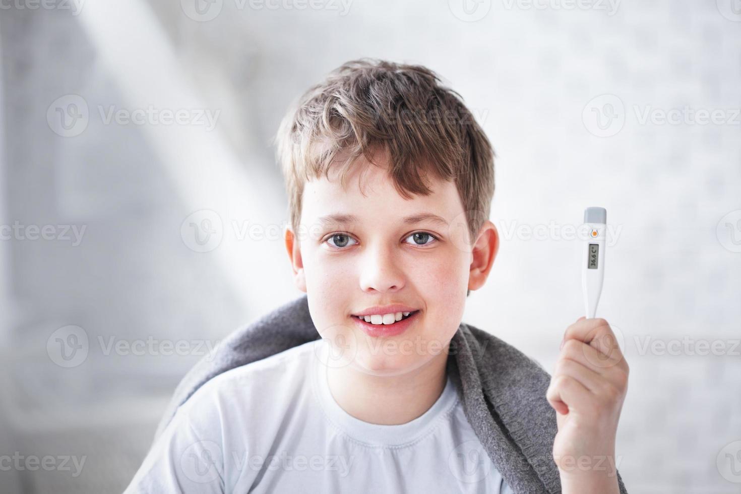 herstelde jongen toont de thermometer foto