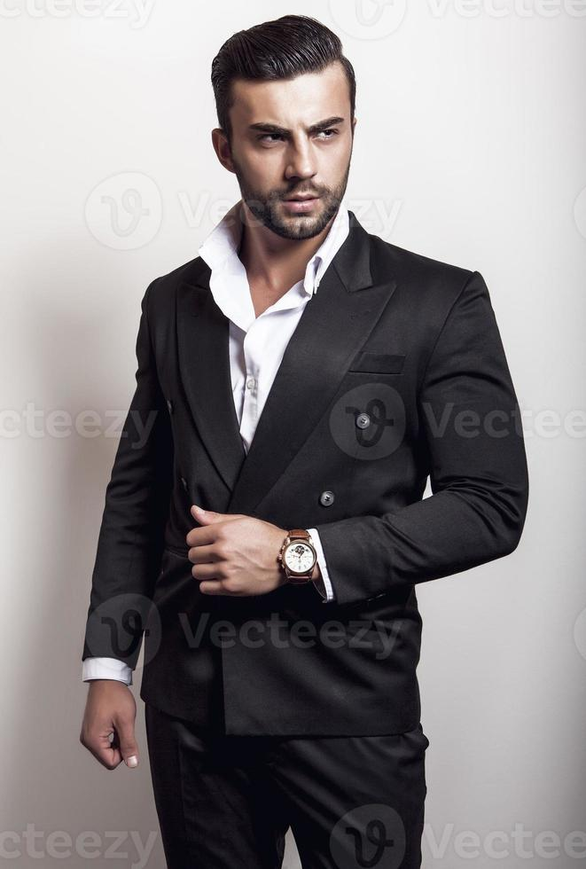 elegante jonge knappe man in zwart klassiek kostuum. foto