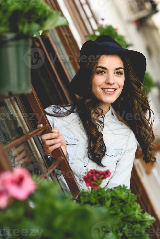 jonge vrouw met hoed in stedelijke achtergrond, het dragen van vrijetijdskleding foto