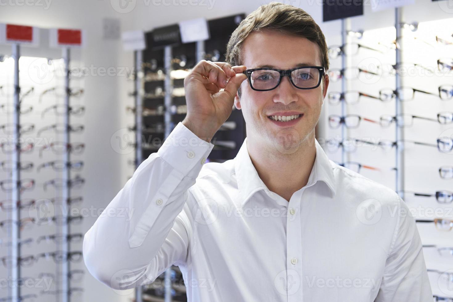 man kiezen nieuwe bril bij opticiens foto