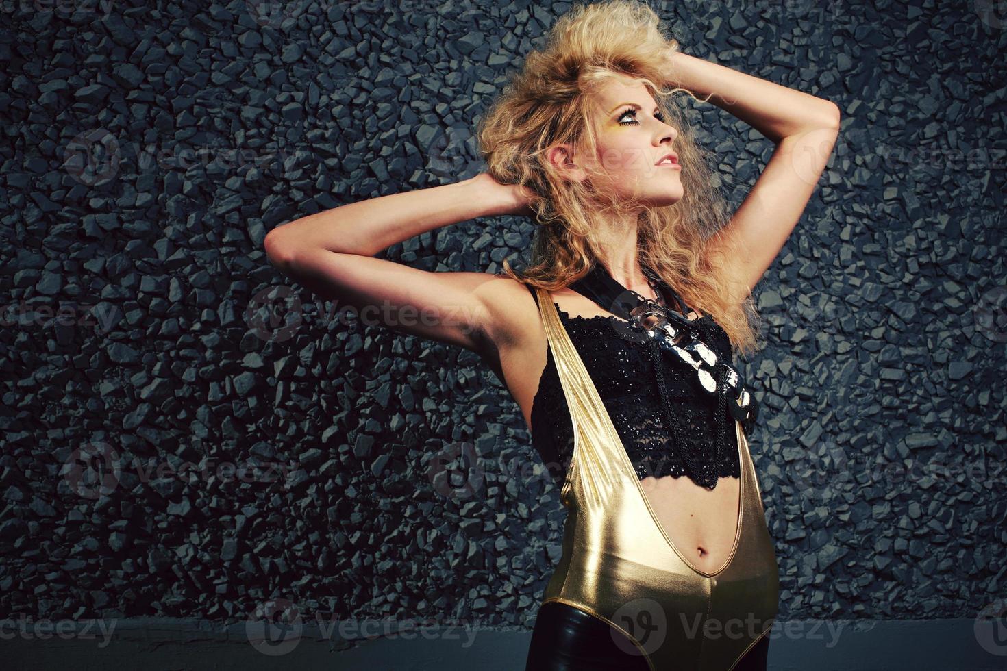 gouden unitard blond meisje op zwart met groot haar foto