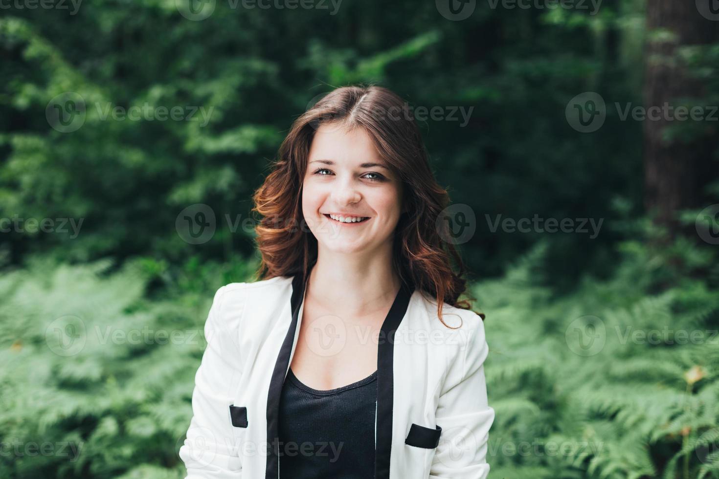 portret van jong gelukkig schoonheidsmeisje in jasje in bos foto