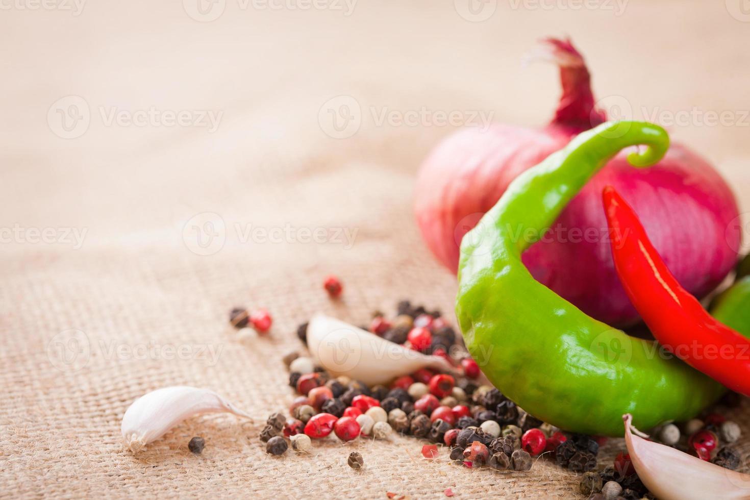 uien, knoflook, chilipeper en kruiden op tafel foto