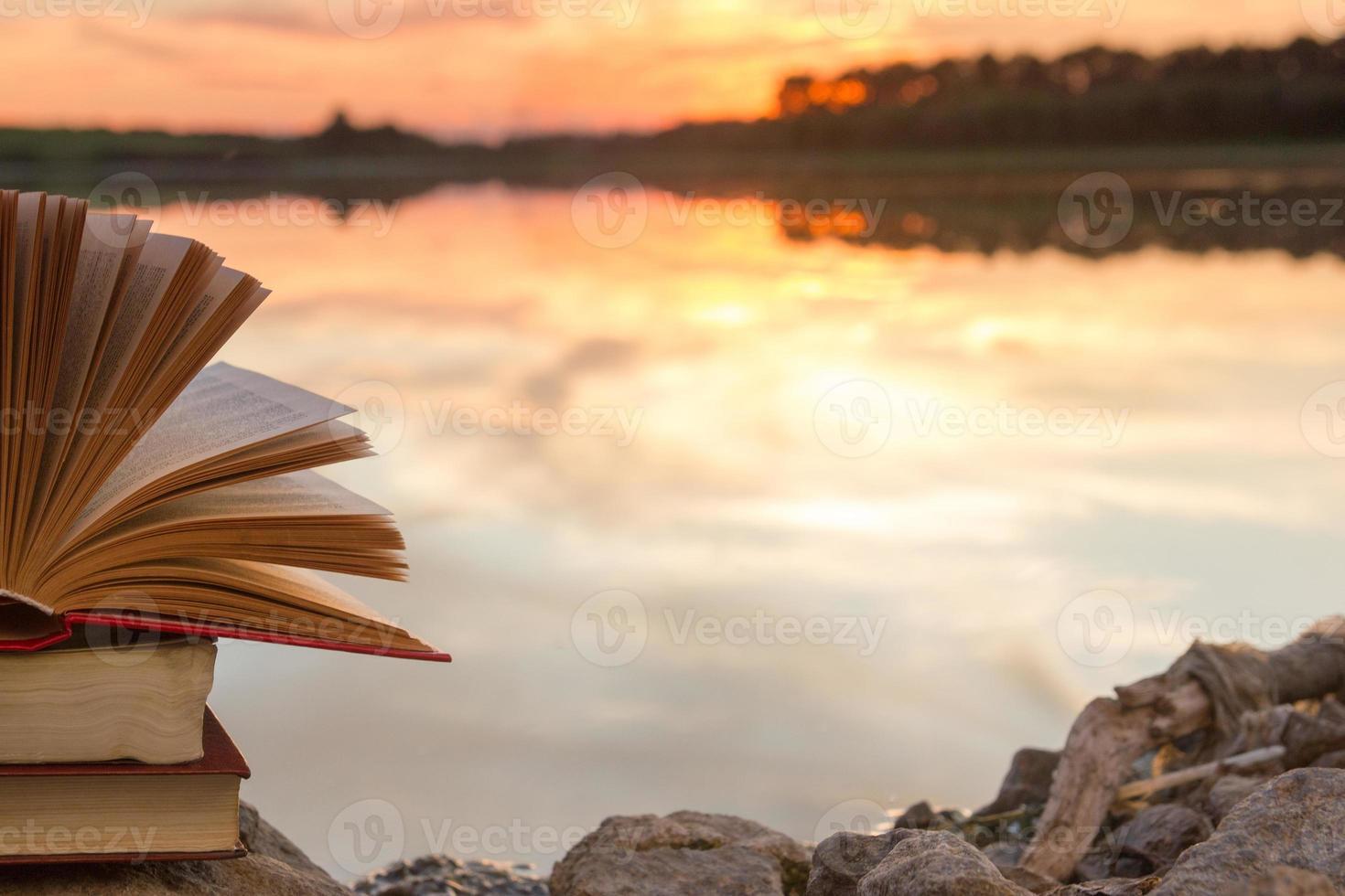 stapel hardcover boek, open boek over wazig natuurlandschap foto