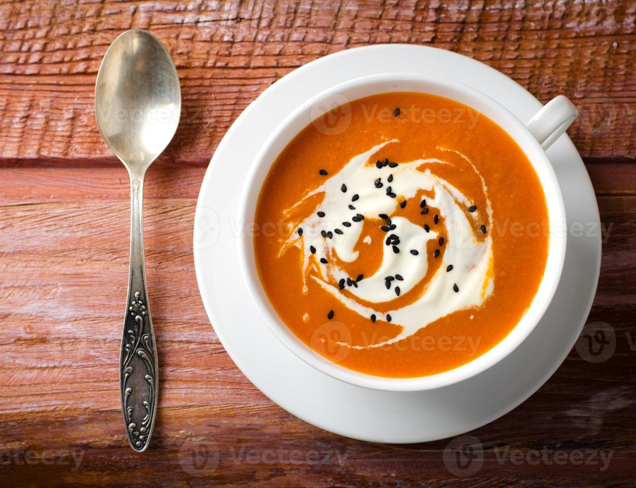 pompoensoep met tomaten, chili, yoghurt en zwarte sesamzaadjes foto