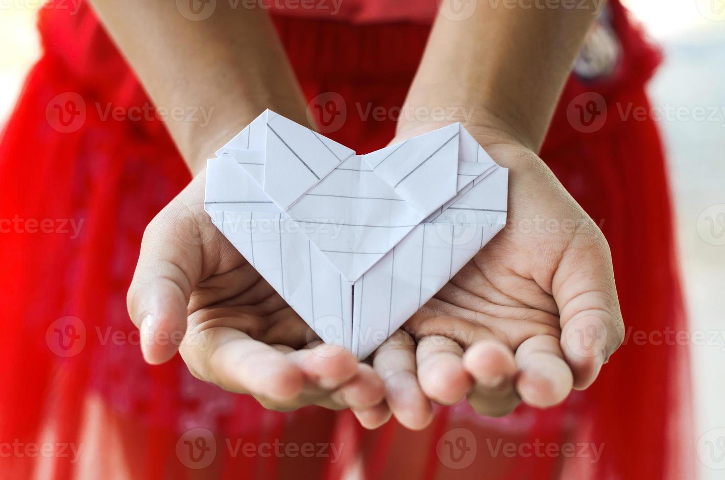 papier hart aan de hand van een klein meisje foto
