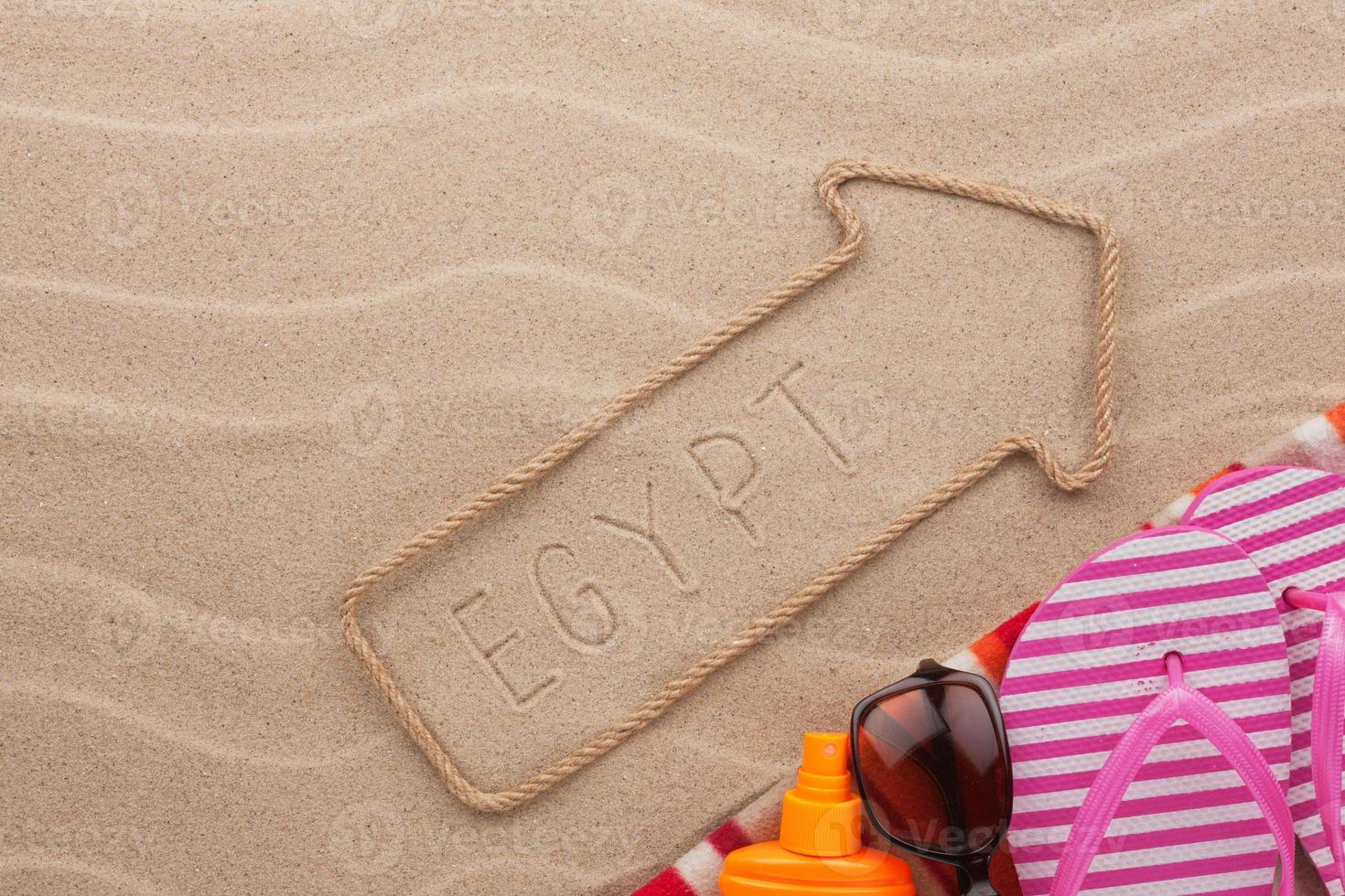 egypte aanwijzer en strandaccessoires die op het zand liggen foto