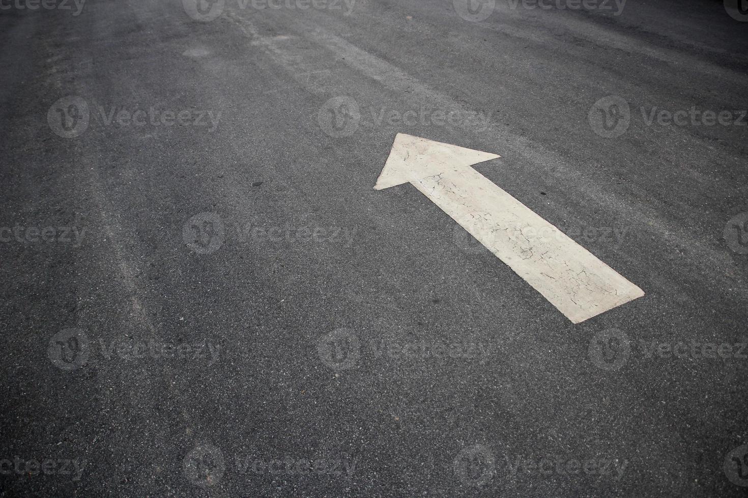witte pijl op het asfalt foto
