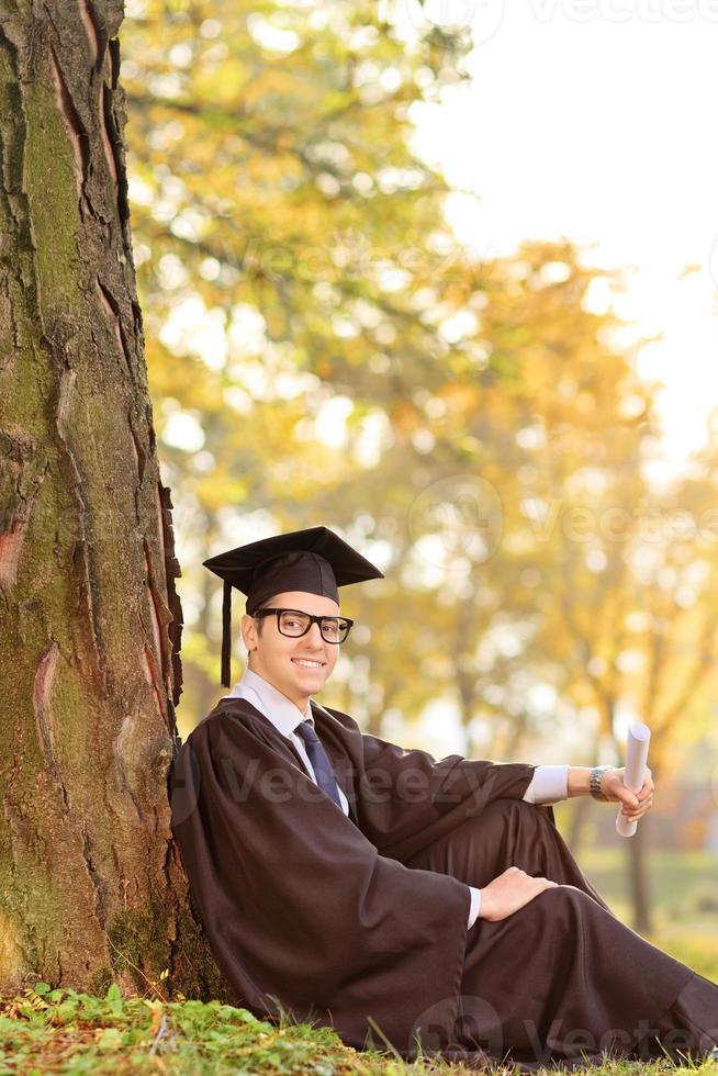 afgestudeerde zit bij een boom in een park foto