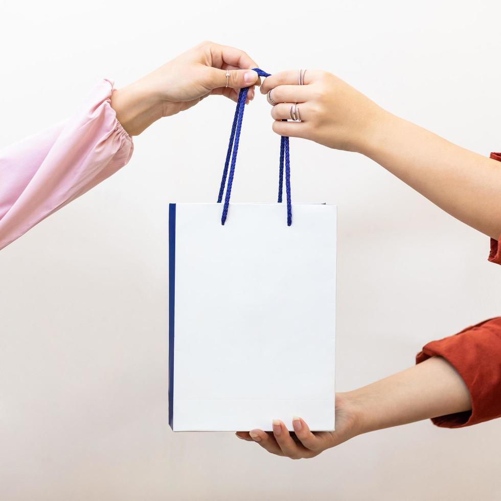 vrouw die een boodschappentas geeft aan een andere persoon foto