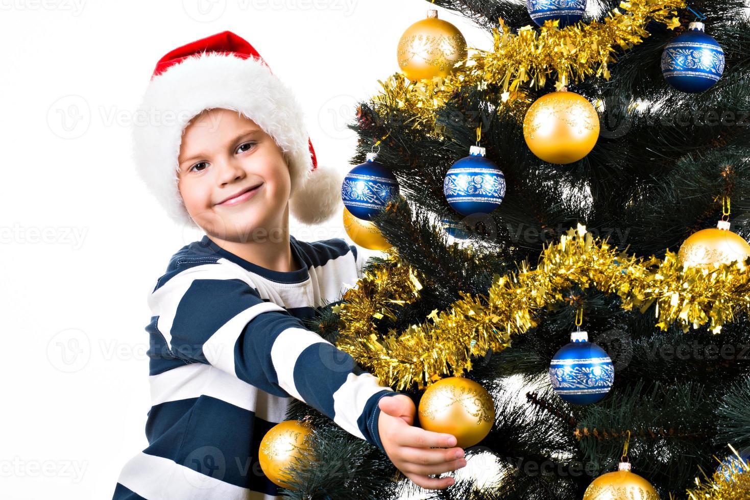 gelukkig kind met cadeau in de buurt van de kerstboom foto