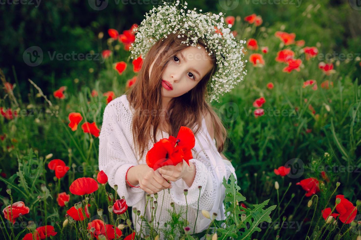 mooi klein meisje poseren in de kroon van een rok van papavers foto