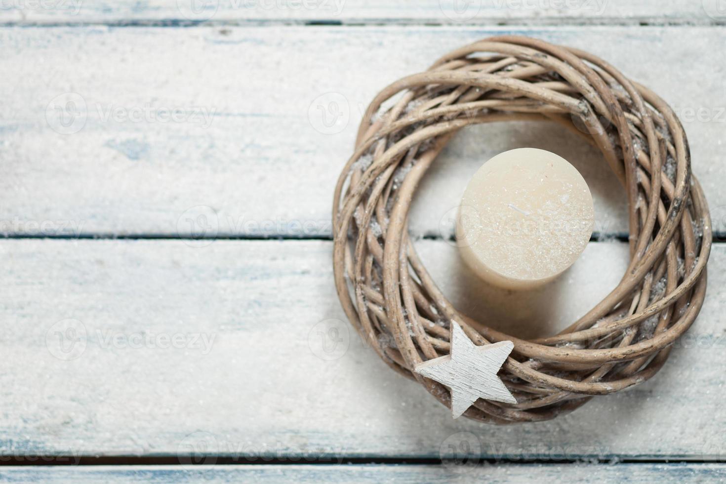 komstkroon met witte kaars, houten ster op hout foto