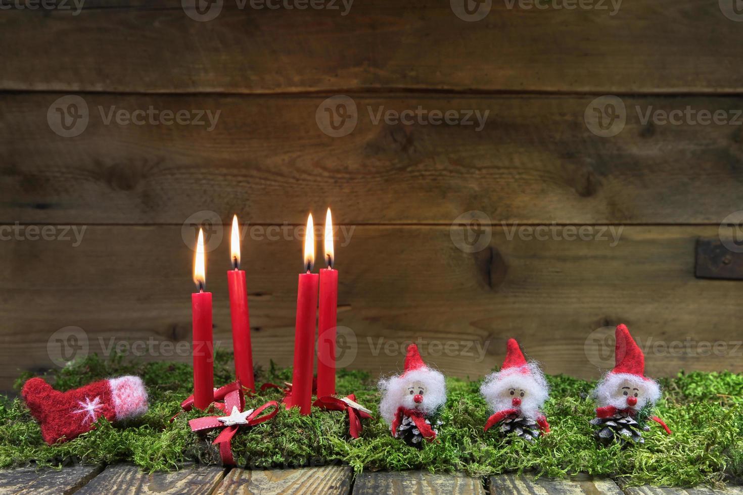 vier rode brandende kerst kaarsen op houten achtergrond. foto