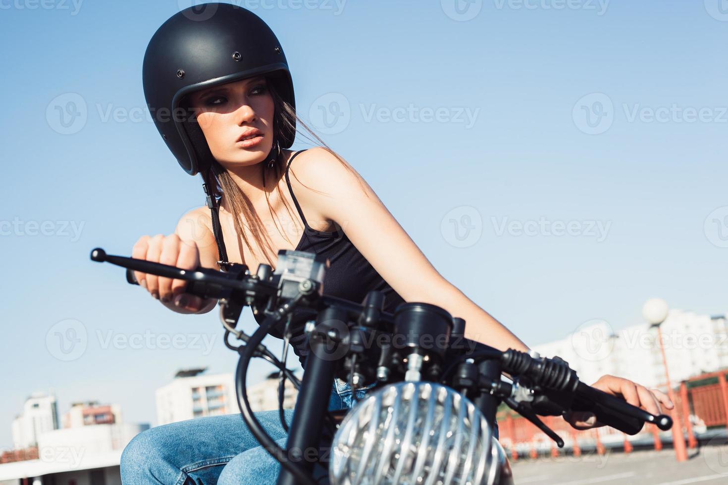 biker meisje zittend op vintage aangepaste motorfiets foto