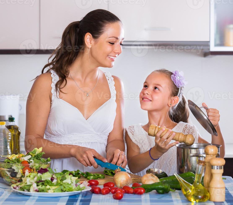 vrouw en meisje koken groenten foto