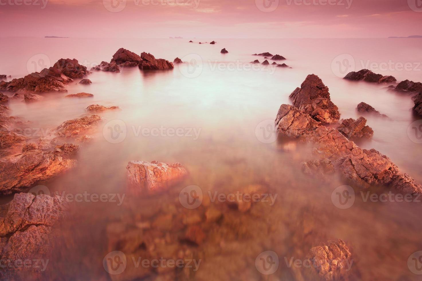 rotsachtig strand bij zonsondergang. foto