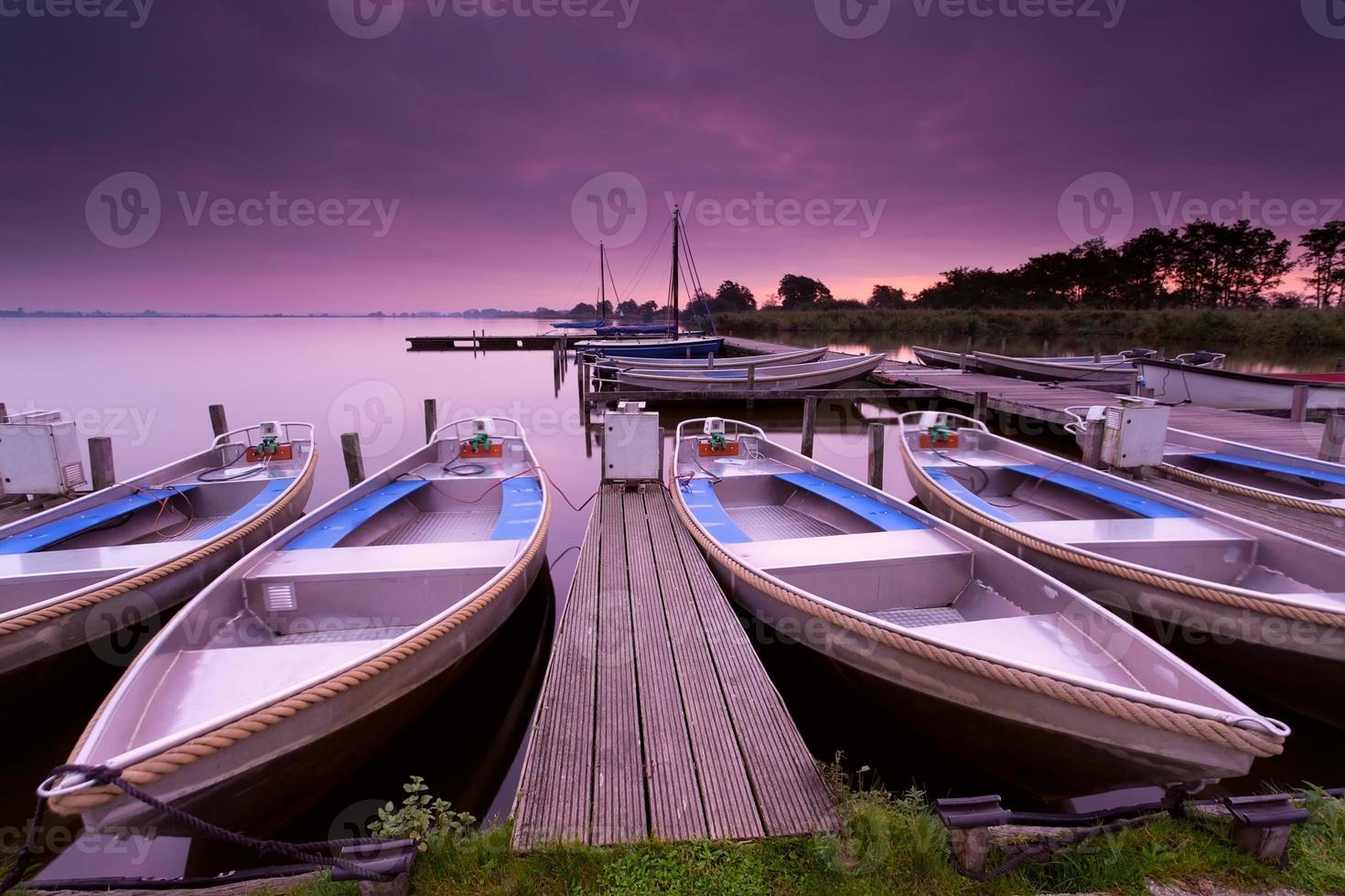 boten door pier op lake haven tijdens zonsopgang foto