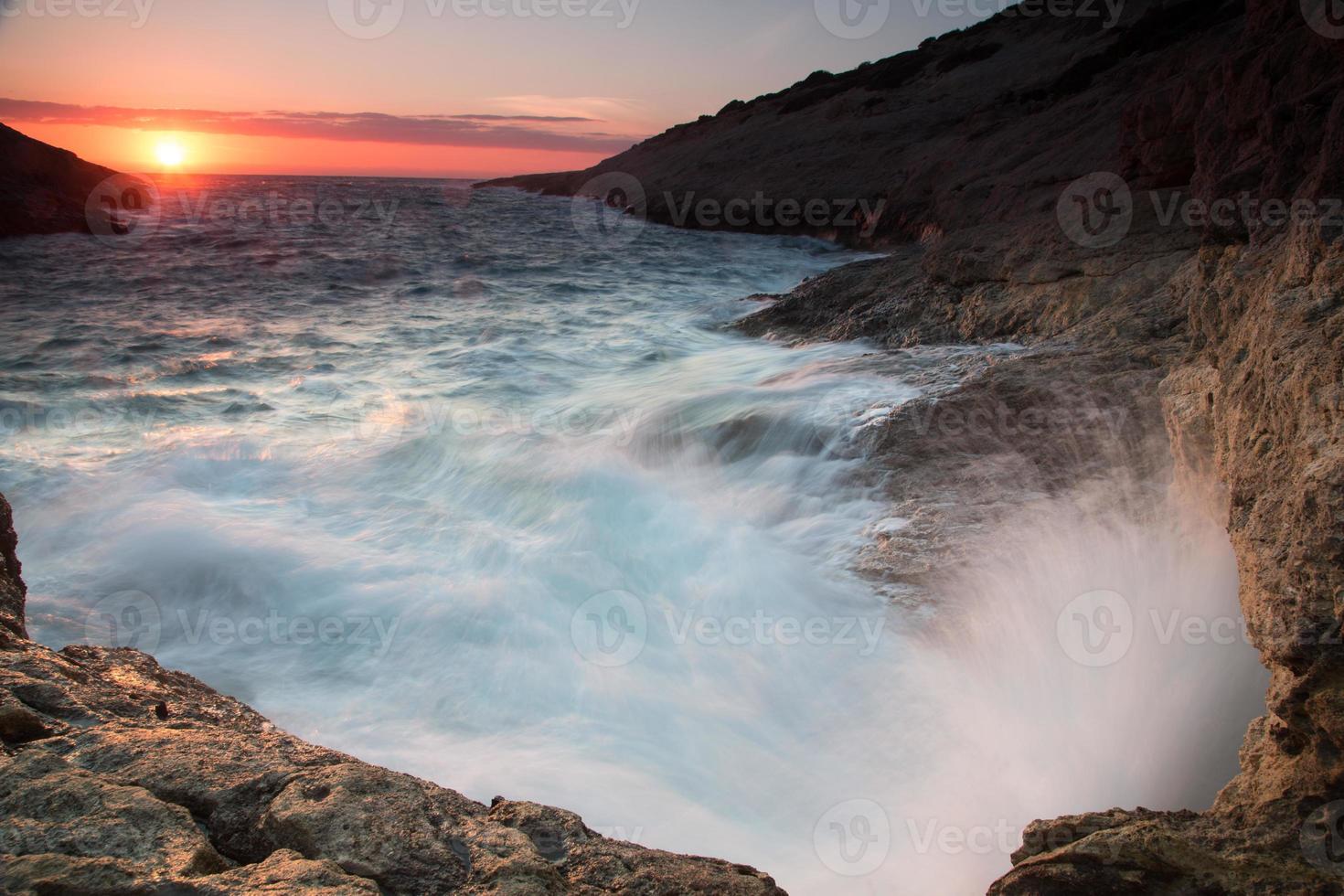 golven breken op een rotsachtige kust bij zonsondergang foto