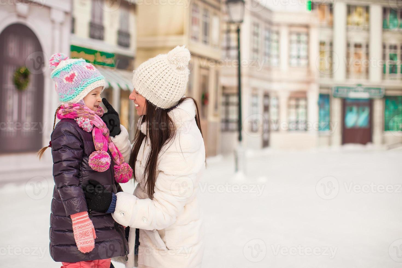 schattig klein meisje en haar jonge moeder op de ijsbaan foto
