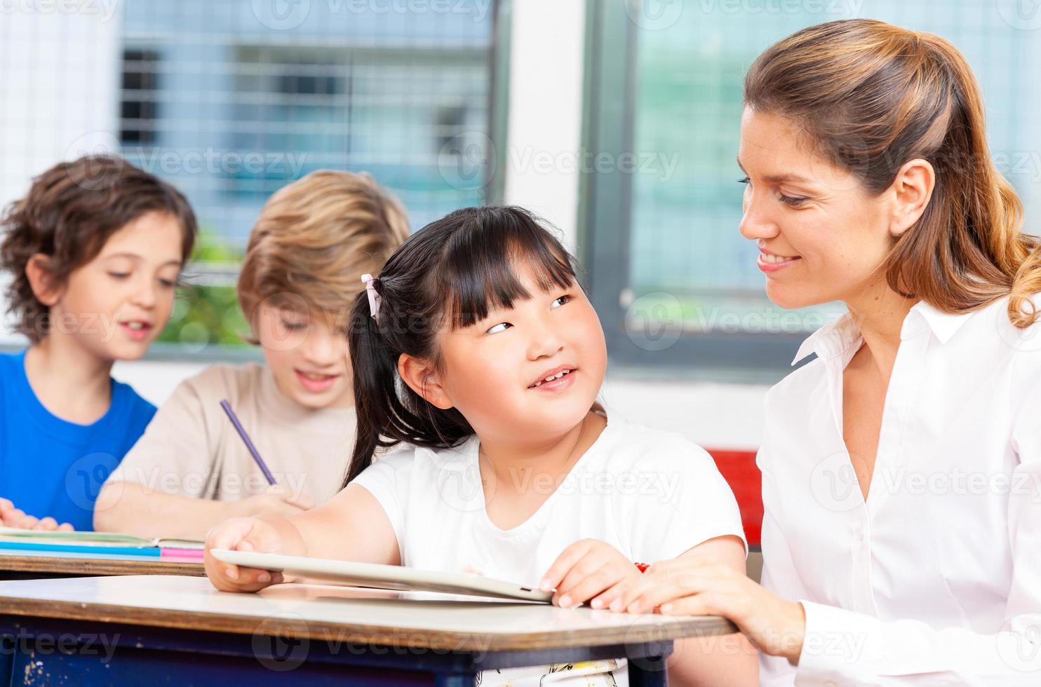 gelukkige elementaire multi-etnische studenten met leraar foto