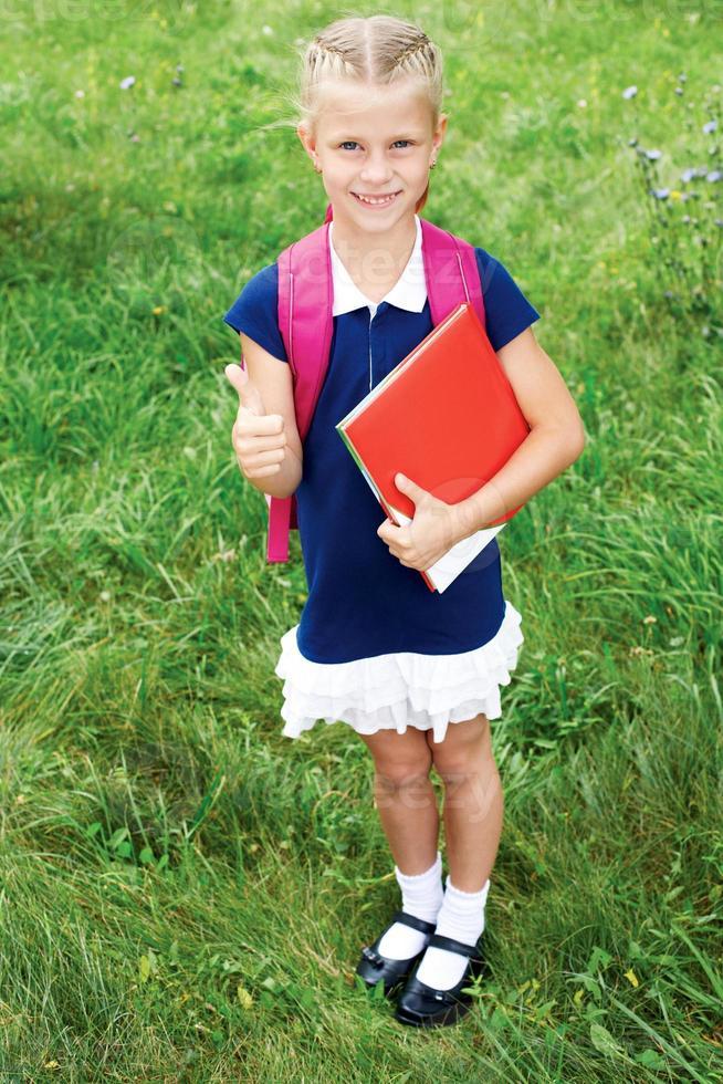 het meisje heeft een schooltas en boeken. foto