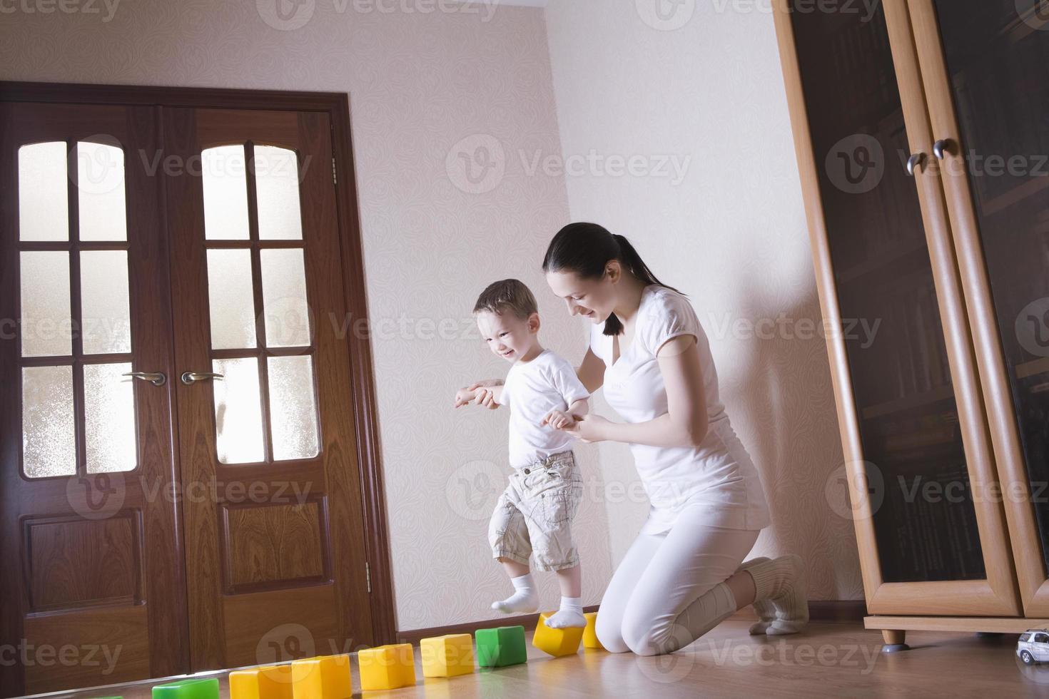 moeder helpt zoon lopen op kubussen foto