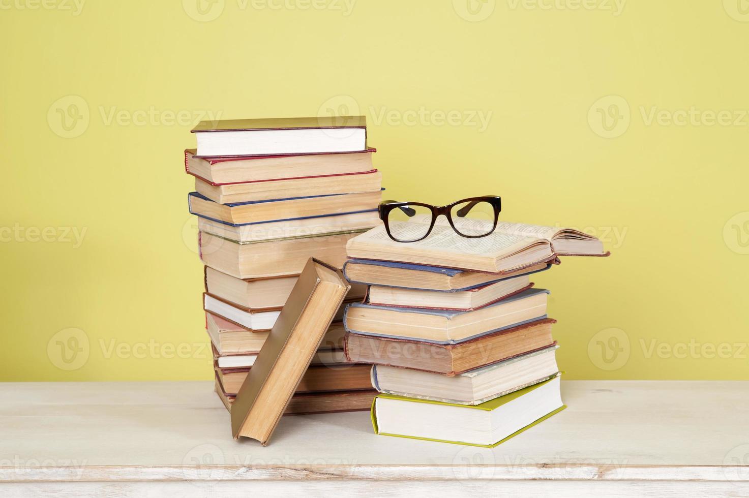 stapel boeken en glazen op een houten tafel. foto
