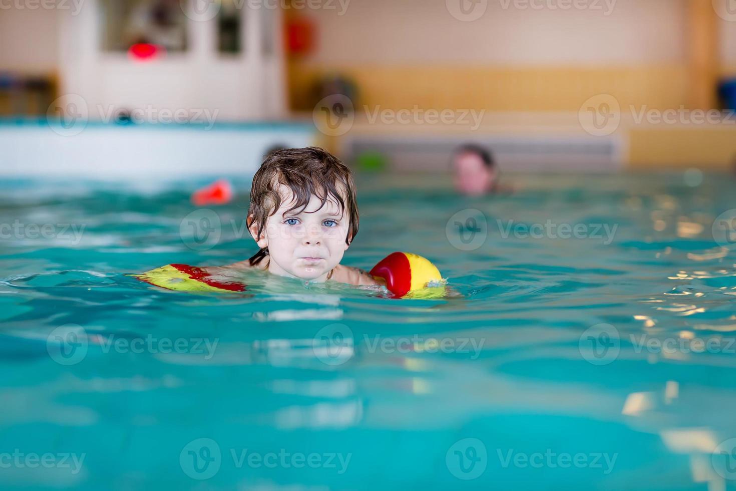 kleine jongen jongen met swimmies leren zwemmen foto