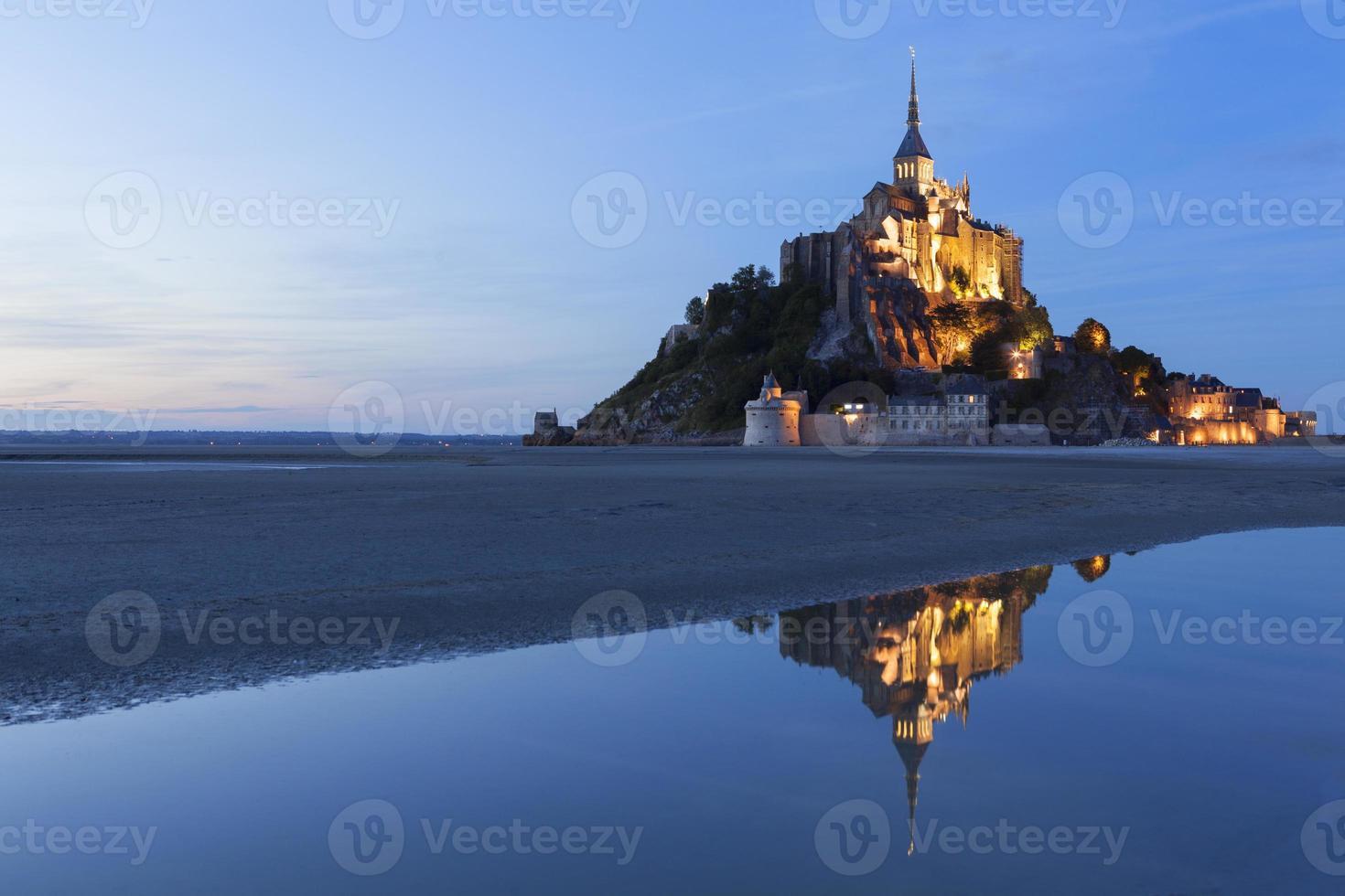 de berg heilige michael verlichtte en weerspiegelde in het water foto