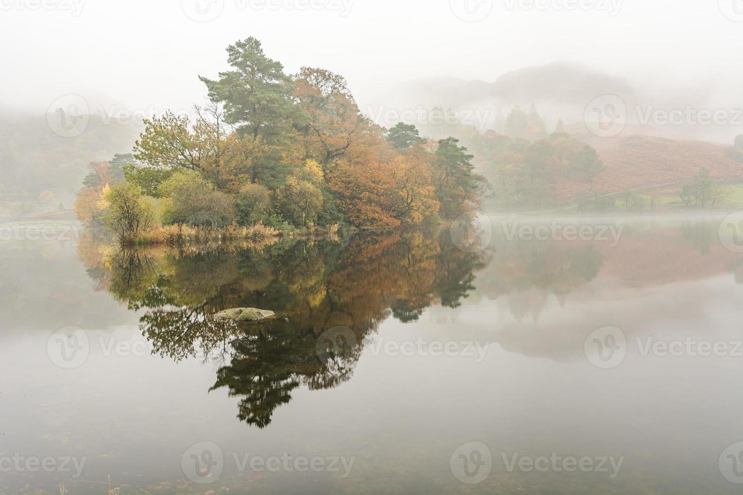 mooie reflecties op rydal water op een mistige ochtend in de herfst. foto