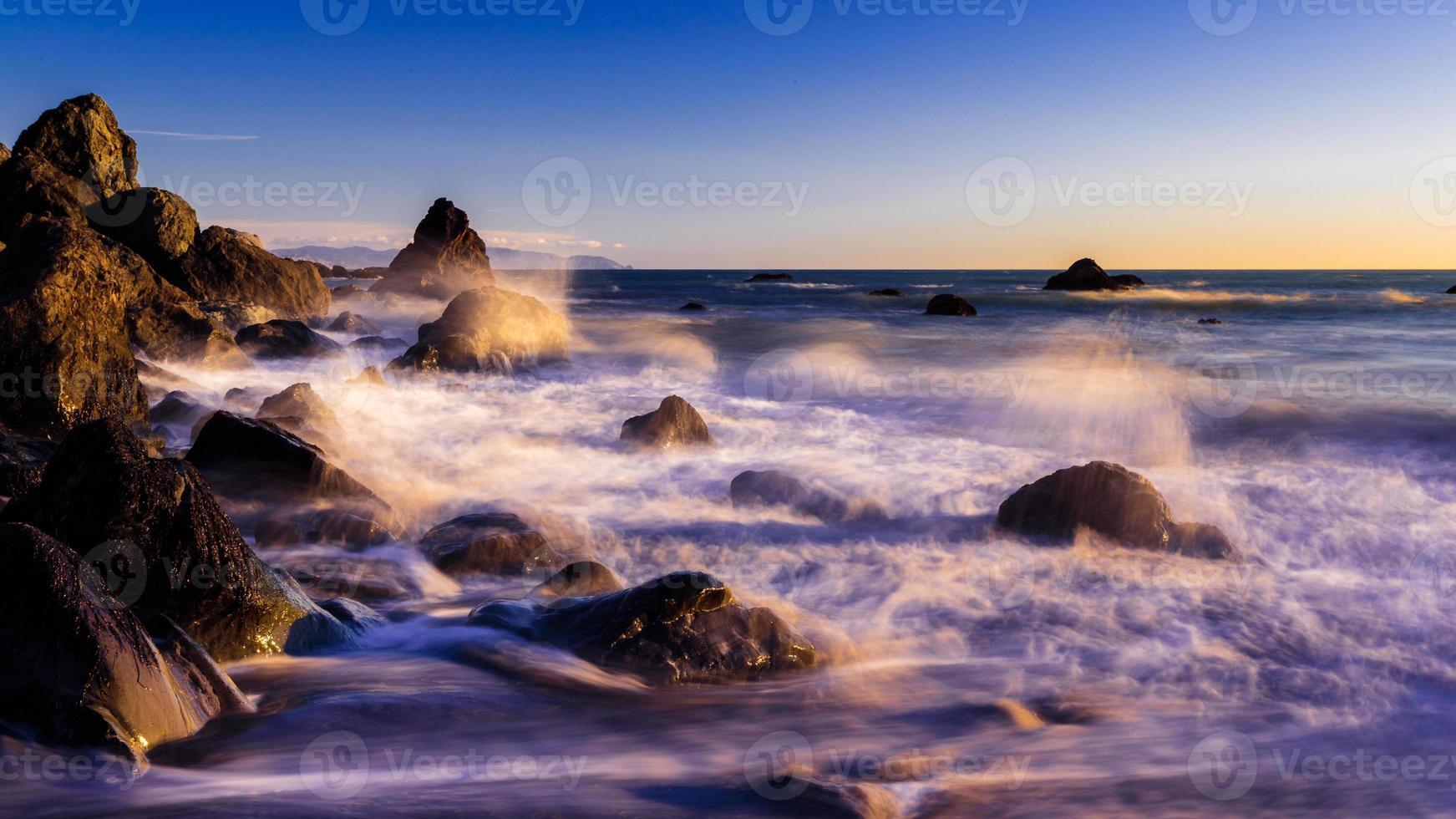 beukende golven op het dromerige strand van Californië bij zonsondergang foto