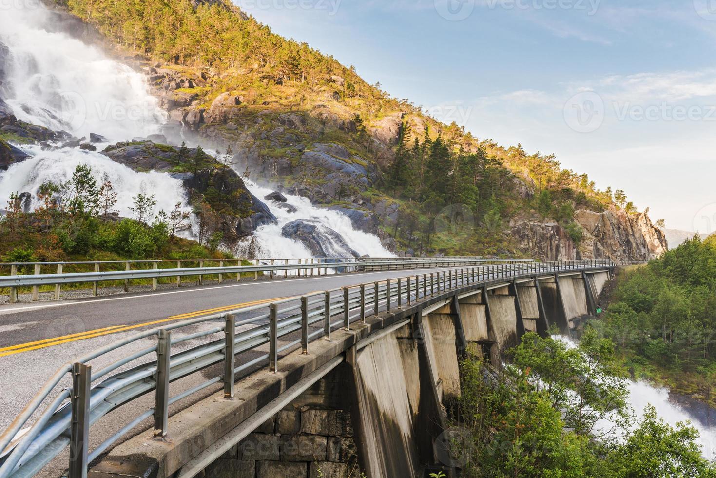 weg in noorwegen die over de waterval langfoss gaat foto